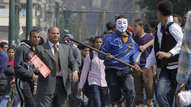 An Egyptian protester wearing a Guy Fawkes mask runs during clashes with security at the entrance of Tahrir Square, the focal point of the Egyptian revolution, in Cairo, Egypt, Tuesday, March 5, 2013. Police briefly cleared protesters from Tahrir Square, once the epicenter of protests against Mubarak. The demonstrators, who have held a sit-in there for the past three months, returned soon after, burning two police vehicles on Sunday, March 3, 2013. (AP Photo/Amr Nabil)