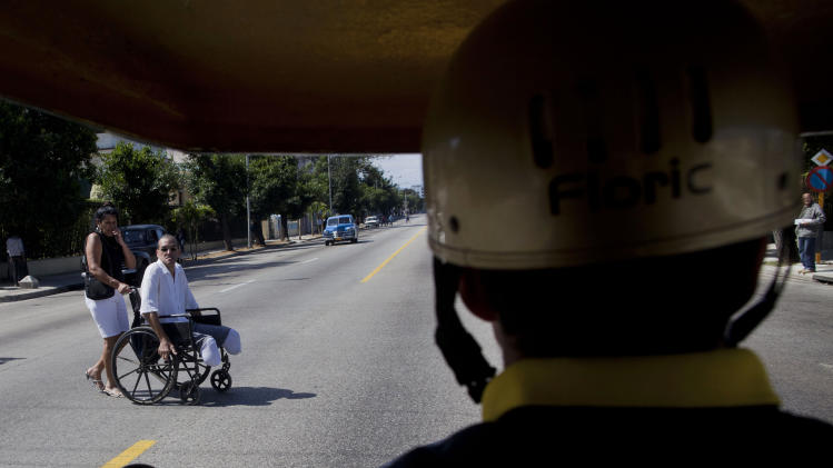 A man in a wheelchair crosses a street in Havana, Cuba, Monday, March 4, 2013. Authorities say they are trying to do something about the lack of caution by jaywalkers, which they say contributes to hundreds of pedestrians being struck each year. (AP Photo/Ramon Espinosa)