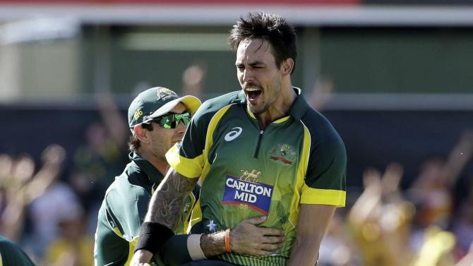 Australia's Mitchell Johnson celebrates with team mate Glenn Maxwell after taking the wicket of England's Eoin Morgan during their One Day International tri-series cricket final match at the WACA ground