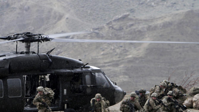 A U.S. Black Hawk helicopter arrives to the scene after a NATO helicopter crashed in a field  killing two American service members, near Gerakhel, eastern Afghanistan, Tuesday, April 9, 2013. The U.S.-led International Security Assistance Force said the cause of the crash is under investigation but initial reporting indicates there was no enemy activity in the area at the time. It did not immediately identify the nationalities of those killed. But a senior U.S. official confirmed they were Americans. (AP Photo/Rahmat Gul)