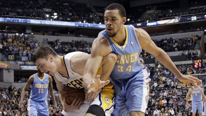 Indiana Pacers forward Tyler Hansbrough, left, tries to keep the ball away from Denver Nuggets center JaVale McGee on an inbounds play during the first half of an NBA basketball game in Indianapolis, Friday, Dec. 7, 2012. (AP Photo/AJ Mast)