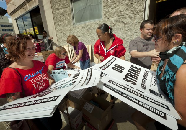 Members of the Chicago Teachers Union distribute strike signage at the Chicago Teachers Union strike headquarters on Saturday, Sept. 8, 2012 in Chicago. The union has vowed to strike on Monday, Sept. 10, 2012, should it fail to reach an agreement over teachers&#39; contracts with Chicago Public Schools by that date. (AP Photo/Sitthixay Ditthavong)
