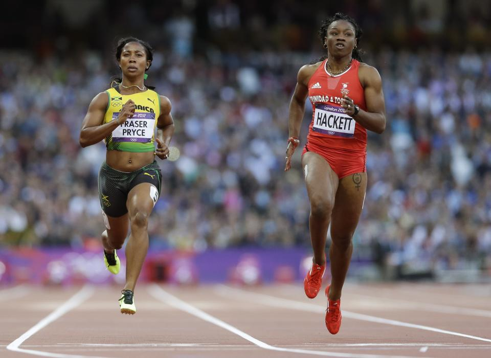 Jamaica's Shelly-Ann Fraser-Pryce, left, and Trinidad's Semoy Hackett go to cross the finish line in a women's 100-meter heat during the athletics in the Olympic Stadium at the 2012 Summer Olympics, London, Friday, Aug. 3, 2012. (AP Photo/Anja Niedringhaus)