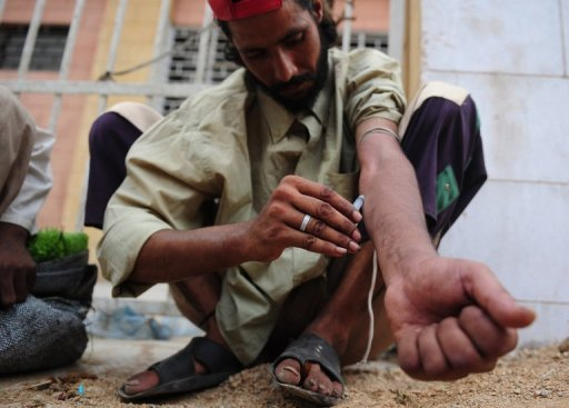 <p>A Pakistani heroin addict self-injects on a street in Karachi. Some 27 million people worldwide are problem drug users, with almost one percent every year dying from narcotics abuse, while cannabis remains the most popular drug, a UN report showed Tuesday.</p>