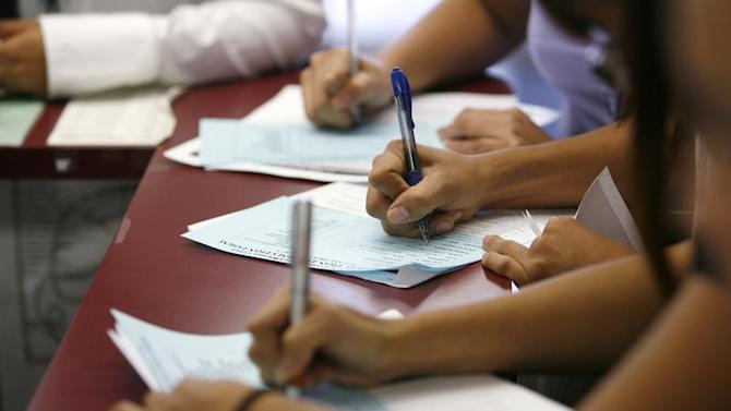Applicants fill out forms during a job fair at the Southeast LA-Crenshaw WorkSource Center in Los Angeles