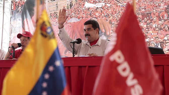 Venezuela's President Nicolas Maduro (C) waves to supporters during a meeting with workers at an oil well operated by Venezuela's state oil company PDVSA in Morichal, Venezuela