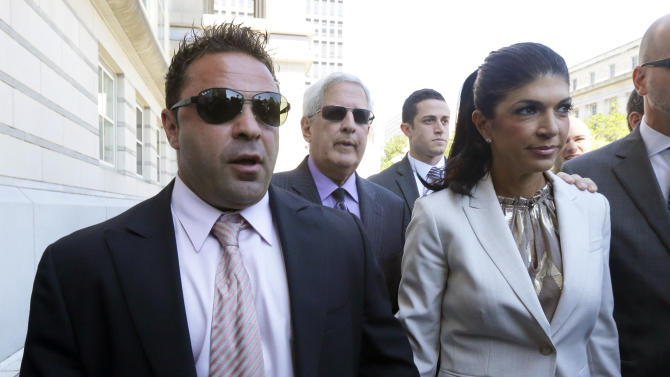 """Giuseppe """"Joe"""" Giudice, 43, left, and his wife, Teresa Giudice, 41, of Montville Township, N.J., walk out of Martin Luther King, Jr. Courthouse after a court appearance, Tuesday, July 30, 2013, in Newark, N.J. The two stars of the """"Real Housewives of New Jersey"""" were indicted Monday on federal fraud charges, accused of exaggerating their income while applying for loans before their TV show debuted in 2009, then hiding their improving fortunes in a bankruptcy filing after their first season aired. They are charged in a 39-count indictment with conspiracy to commit mail and wire fraud, bank fraud, making false statements on loan applications and bankruptcy fraud. (AP Photo/Julio Cortez)"""