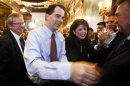 FILE - In this June 6, 2012 file photo, Wisconsin Gov. Scott Walker, second from left, and Lt. Gov. Rebecca Kleefisch are greeted by the governor's cabinet and staff at the Wisconsin State Capitol in Madison a day after Walker won a recall election. Another year, another campaign. Walker is gearing up for re-election next year, his third race in four years. But his courting of outside-the-state donors and conservatives, plans to visit Iowa this week and refusal to say whether he would serve out another full term suggest he might be seeking a much bigger prize _ the presidency. (AP Photo/Andy Manis, File)