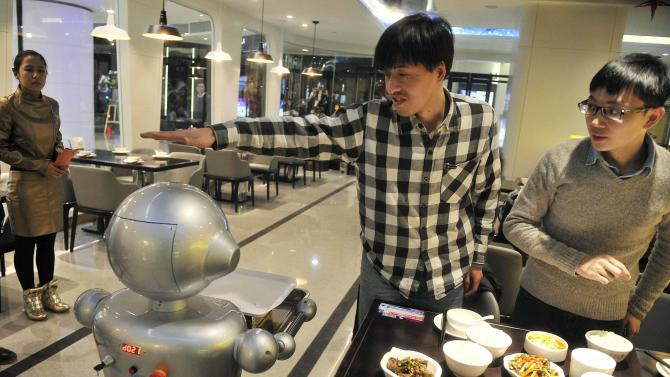 A man gestures to a robot at a restaurant in Hefei