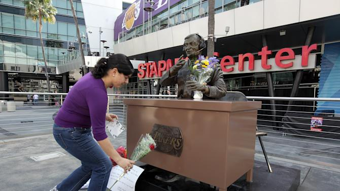Lakers fan Jeannette Hernandez, lays a flower at the statue of the late Laker announcer Chick Hearn for Lakers' owner Jerry Buss at the Staples Center in downtown Los Angeles on Monday Feb. 18,2013. Buss, the Los Angeles Lakers'  owner who shepherded the NBA team to 10 championships from the Showtime dynasty of the 1980s to the Kobe Bryant era, died Monday. He was 80. (AP Photo/Richard Vogel)