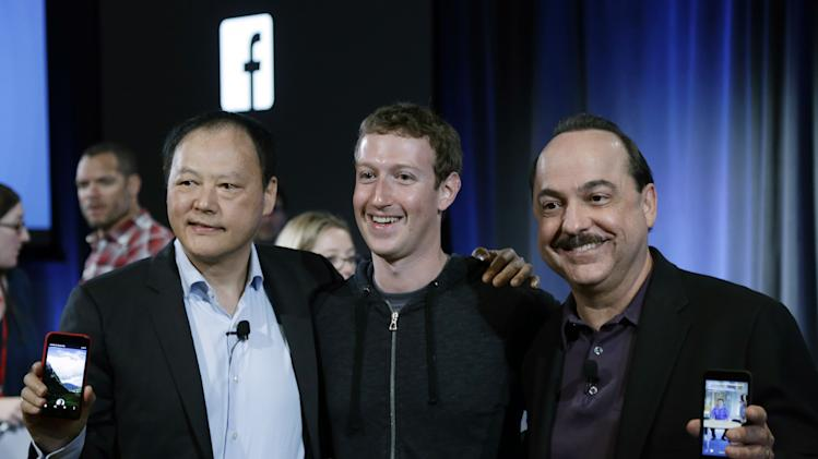 From left, HTC CEO Peter Chou, Facebook CEO Mark Zuckerberg and AT&T Mobility CEO Ralph De La Vega embrace as they show joint products at Facebook headquarters in Menlo Park, Calif., Thursday, April 4, 2013. (AP Photo/Marcio Jose Sanchez)