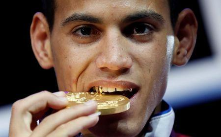 Gold medallist Robeisy Ramirez Carrazana of Cuba bites his medal during the presentation ceremony for the Men's Fly (52kg) boxing competition at the London Olympics