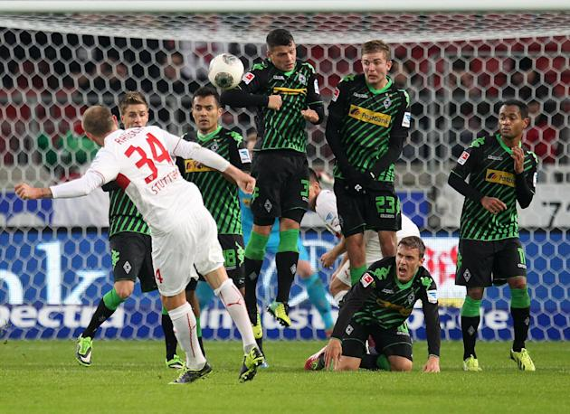 Stuttgart's Konstantin Rausch, left,  shoots a free kick against Moenchengladbach's defense, during the German first division Bundesliga soccer match between VfB Stuttgart and Borussia Moenchengladbac