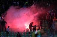 Flares are thrown in the stadium during clashes after a football match between Egypt&#39;s Al-Ahly and Al-Masry teams in Port Said, on February 1, 2012. A 13-year-old boy has been shot dead when Egyptian security forces clashed with fans protesting against a ban on Al-Masry football club over the deadly stadium riot