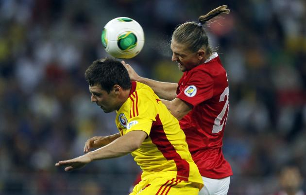 Turkey's Erkin jumps for the ball with Romania's Popa during their 2014 World Cup qualifying soccer match at National Arena in Bucharest