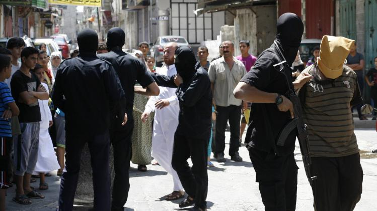 A Hamas militant grabs a Palestinian suspected of collaborating with Israel in Gaza City