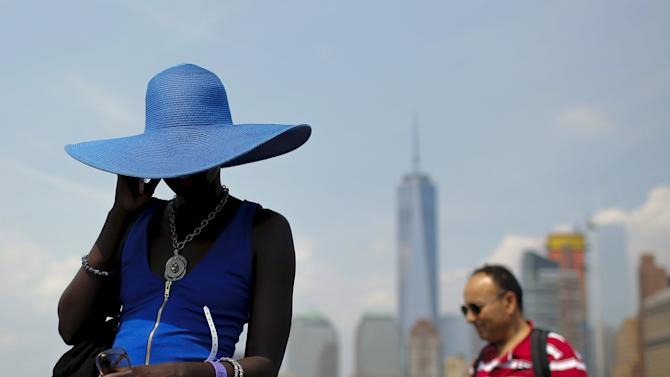 A woman covers herself from the sun with a blue hat during a hot summer day in New York