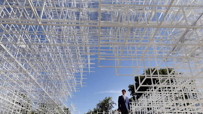 AP10ThingsToSee - A journalist stands inside the Serpentine Gallery 2013 Pavilion, designed by Japanese architect Sou Fujimoto, in central London's Kensington Gardens, Tuesday, June 4, 2013. Occupying some 357 square-meters of lawn in front of the Serpentine Gallery, 41-year-old Fujimoto's structure of 20mm steel poles features a cafe and visitors will be encouraged to enter and interact with the piece in different ways. (AP Photo/Lefteris Pitarakis)