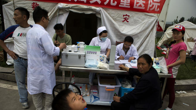 Residents seek medical service at a make shift hospital at the county seat of Lushan in southwestern China's Sichuan province, Sunday, April 21, 2013. Rescuers and relief teams struggled to rush supplies into the rural hills of China's Sichuan province Sunday after the earthquake prompted frightened survivors to spend a night in cars, tents and makeshift shelters. (AP Photo/Ng Han Guan)