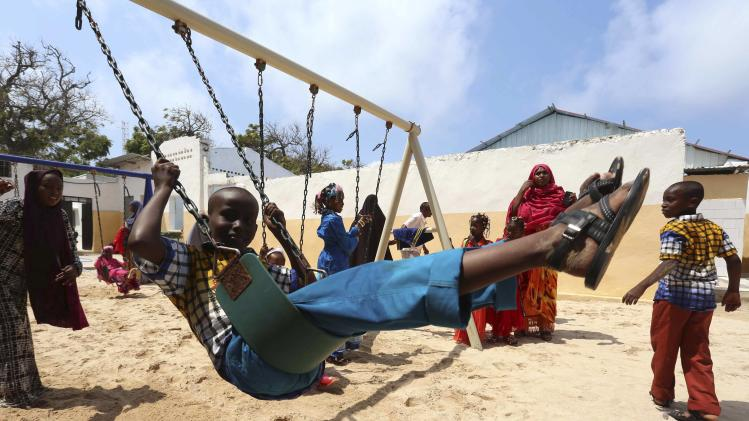 Children swing in celebration after attending Eid al-Fitr prayers to mark the end of the fasting month of Ramadan in Somalia's capital Mogadishu