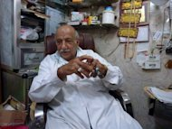 Iraqi Salman al-Khafaji sits at his clinic in central Baghdad on June 27. Dozens of patients flock to the clinic of the former nurse each day, believing the octogenarian would end the suffering from the burns and skin diseases that doctors fail to treat