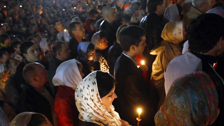 Orthodox devotees carry candles during Easter Sunday rites in Donetsk, Ukraine, early Sunday, April 20, 2014. (AP Photo/Sergei Grits)