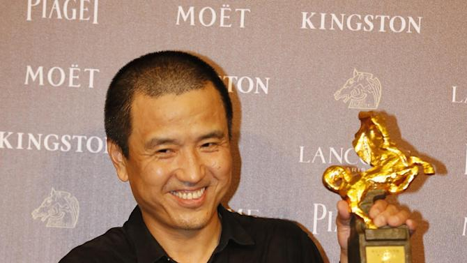 "Chinese director Lou Ye holds his award and poses for media for Best Feature Film ""Blind Massage"" at the 51st Golden Horse Awards in Taipei, Taiwan, Saturday, Nov. 22, 2014. The Golden Horse awards are the Chinese-language film industry's biggest annual events. (AP Photo/Wally Santana)"