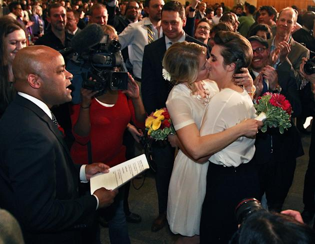 Just after midnight, Denver Mayor Michael Hancock, left, performs a civil union vows ceremony for Sonja Semion, center left, and her partner Courtney Law at the Webb Municipal Building in Denver, Wedn