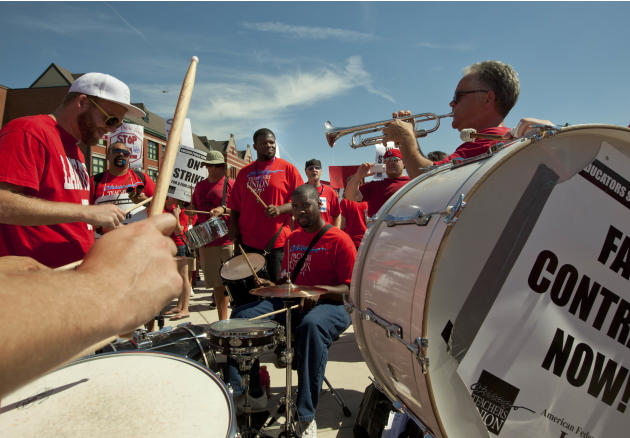 A band entertains a large group of public school teachers as they march past John Marshall Metropolitan High School on Wednesday, Sept. 12, 2012 in West Chicago. Teachers walked off the job Monday for