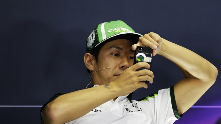 Caterham Formula One driver Kobayashi of Japan takes a picture during a news conference at the Hungaroring circuit, near Budapest