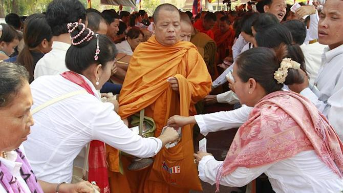 MAK01. Phnom Penh (Cambodia), 30/03/2015.- Relatives of victims who died in a grenade attack in 1997 give offerings to Buddhist monks during a ceremony in Phnom Penh, Cambodia, 30 March 2015. Victims' families hold the ceremony to pray for their relatives who died in the grenade attack during a political rally at a park in Phnom Penh eighteen years ago. (Atentado, Camboya) EFE/EPA/MAK REMISSA