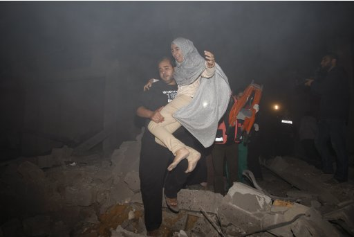 Palestinian man evacuates a woman following Israeli air strikes in Gaza