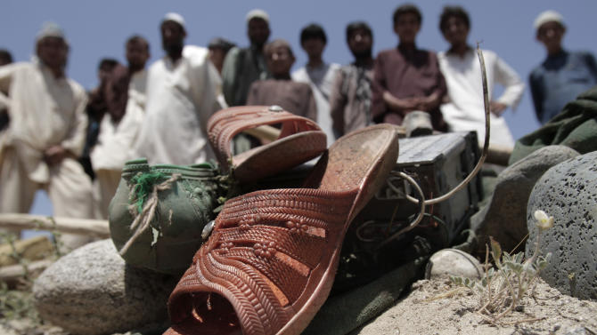 Afghans look at shoes that remained at the scene after a vehicle was hit by a road side bomb in the Alingar district of Laghman province, east of Kabul, Afghanistan, Monday, June 3, 2013. A statement from the provincial government said a group of four women and two children had gone with a male driver into the hills to collect firewood. On their way back, their vehicle hit the mine and all inside were killed. (AP Photo/Rahmat Gul)