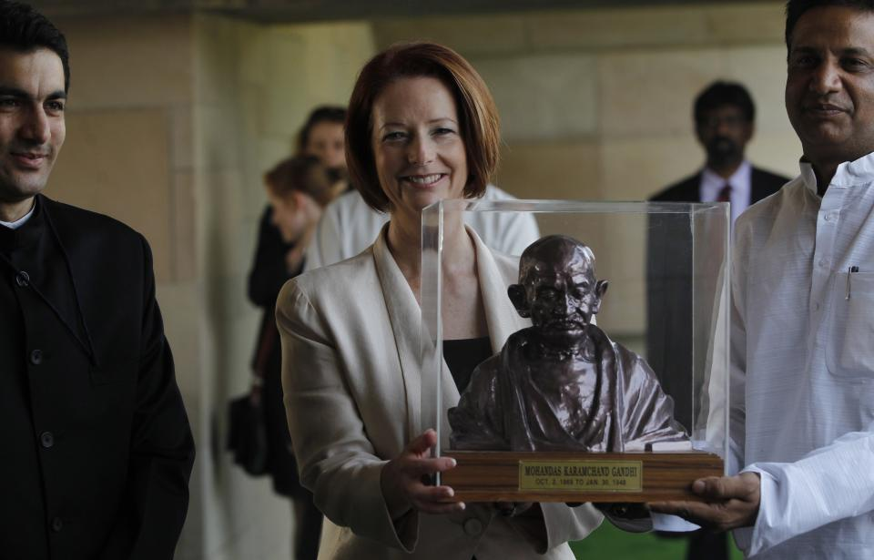 Australian Prime Minister Julia Gillard receives a memento from Rajnish Kumar, Secretary of the Gandhi Samadhi Committee, at the memorial of Mahatma Gandhi in New Delhi, India , Wednesday, Oct. 17, 2012. (AP Photo/Mustafa Quraishi)