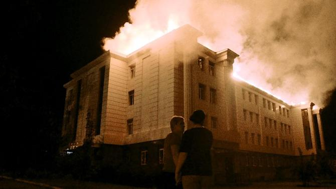 Bystanders watch a fire consuming a school in downtown Donetsk on August 27, 2014, after being hit by shelling