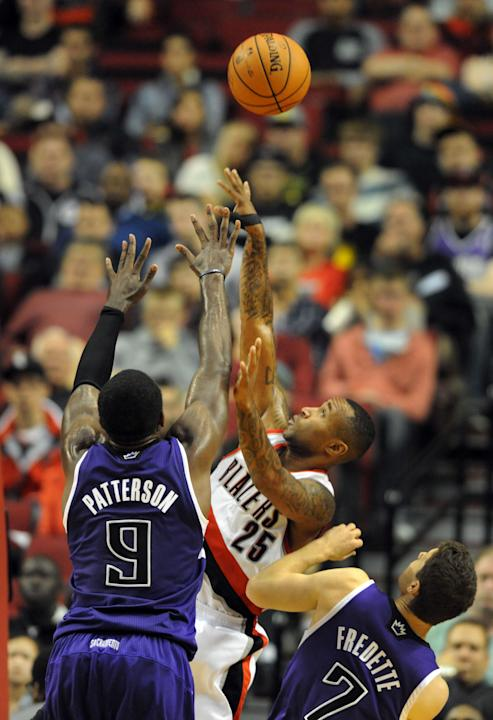 Portland Trail Blazers guard Mo Williams (25) shoots the ball over Sacramento Kings forward Patrick Patterson (9) and Sacramento Kings guard Jimmer Fredette (7) during the second half of an NBA basket