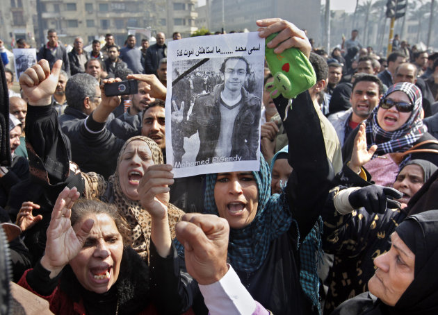 Egyptian relatives of Mohammed el-Gindy, a 28-year-old activist, who died early Monday of wounds sustained during clashes last Friday near the presidential palace, display his picture as they shout anti-president Morsi slogans during his funeral procession in Tahrir Square, Cairo, Egypt, Monday, Feb. 4, 2013. More than 60 people have died in recent protests across Egypt that began on Thursday, Jan. 24, 2013, the eve of the second anniversary of the start of the uprising that toppled autocrat Hosni Mubarak. Arabic reads &quot;my name is Mohammed and I did not deserve to die this way.&quot; (AP Photo/Amr Nabil)