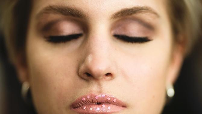 A model poses with her prepared lips prior to the fashion show of designer Lena Hoschek during the Mercedes Benz Fashion Week in Berlin, Tuesday, Jan. 17, 2017. (AP Photo/Markus Schreiber)