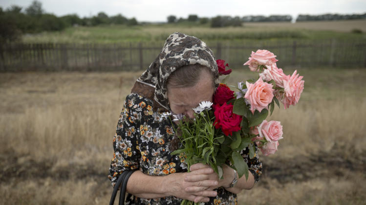 AP10ThingsToSee - A woman cries during a religious service held by villagers in memory of the victims at the crash site of Malaysia Airlines Flight 17, near the village of Hrabove, eastern Ukraine, Tuesday, July 22, 2014. (AP Photo/Vadim Ghirda)