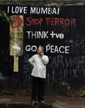 A man talks on his cell phone in front of a graffiti put up after the 2008 terrors attacks outside a Hindu crematorium where some victims of Wednesday's blasts were cremated in Mumbai, India, Thursday, July 14, 2011. There are no immediate suspects in the triple bombing in India's financial capital and the attack came without warning, the country's top security official said Thursday, while shell shocked residents lambasted the government for the apparent intelligence breakdown.(AP Photo/Aijaz Rahi)