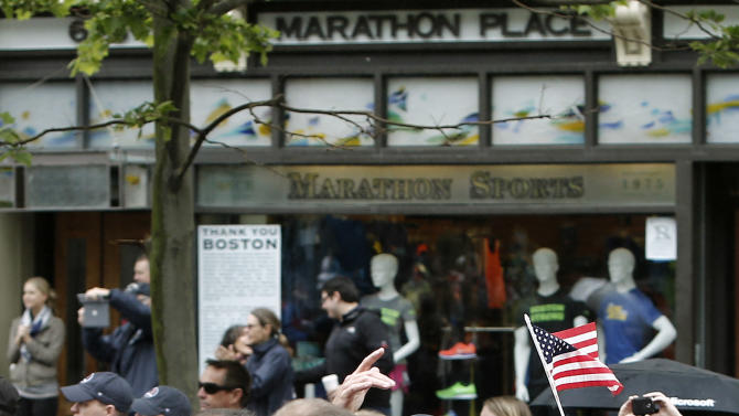 Runners who were unable to finish the Boston Marathon on April 15 because of the bombings pass the first bombing site as they head toward the finish line on Boylston Street after the city allowed them to finish the last mile of the race in Boston Saturday, May 25, 2013. (AP Photo/Winslow Townson)