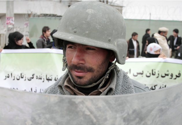 An Afghan riot police officer stands guard during a march calling for end of violence against women in Kabul, Afghanistan, Thursday, Feb. 14, 2013. Dozens of Afghan activists have marked Valentine's D