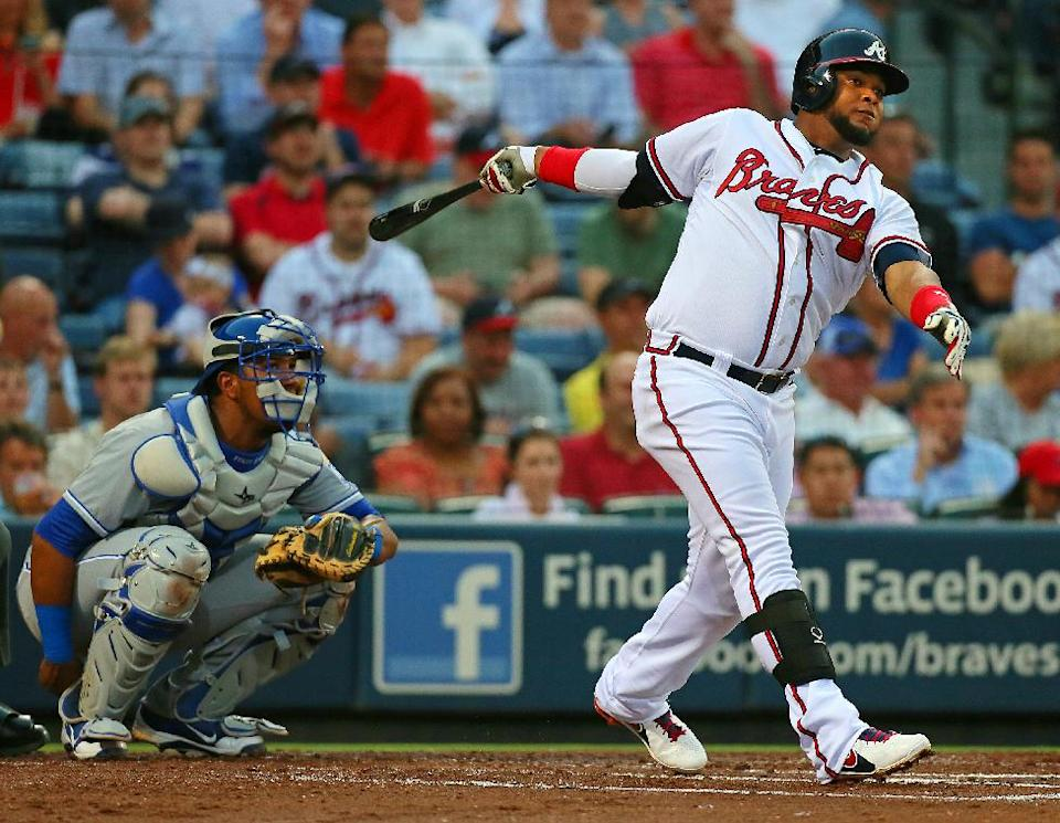 Atlanta Braves Juan Francisco hits a solo home run with Kansas City Royals catcher Salvador Perez looking on during the second inning of a baseball game Tuesday, April 16, 2013, in Atlanta.  (AP Photo/Atlanta Journal-Constitution, Curtis Compton)