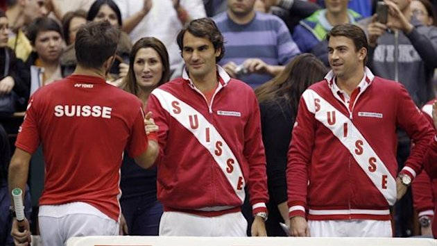 Switzerland's Roger Federer (C) and Michael Lammer (R) congratulate Stanislas Wawrinka (L) after winning his Davis Cup World Group match against Serbia's Dusan Lajovic (Reuters)