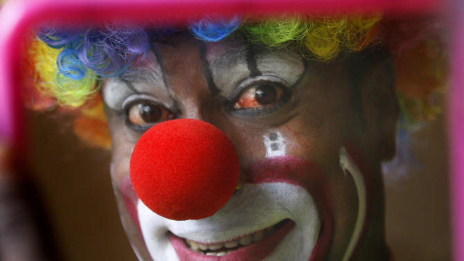 In this April 11, 2013 photo, Biju Nair, principal clown at Rambo Circus, looks at a mirror before a performance on the outskirts of Mumbai, India. Nair who literally ran away and joined the circus at the age of 10 says he scours YouTube for videos of international clowning acts to give him new ideas with help from other performers who know how to read and write, since he never learned. Circuses around the world may struggle to compete with an ever-increasing array of entertainment options, but India's once-widespread industry in particular has gone through cataclysmic changes. (AP Photo/Rafiq Maqbool)