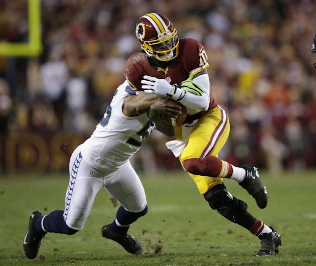 Seattle Seahawks outside linebacker Leroy Hill stops Washington Redskins quarterback Robert Griffin III during the first half of an NFL wild card playoff football game in Landover, Md., Sunday, Jan. 6