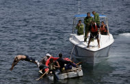 FILE - In this June 4, 2009 file photo, Cuban coast guards, right, stop men from trying to migrate illegally to the U.S. on a foam raft near Havana's Malecon. Cuba's government appears on the verge of a momentous decision that could end a half-century of travel restrictions that make it difficult to leave the Communist-run island, even for vacation. (AP Photo/Javier Galeano, File)
