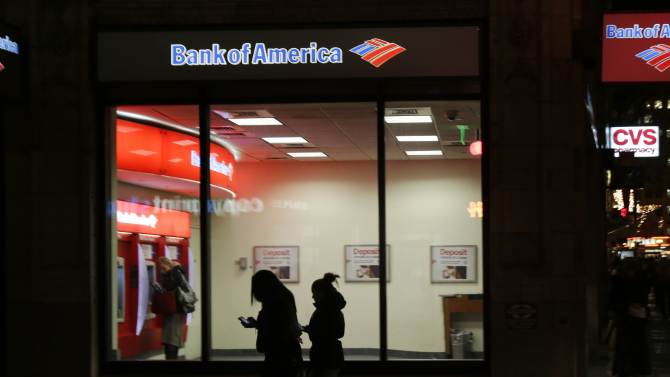 In this Thursday, Dec. 13, 2012 photo people use a Bank of America ATM in Boston. Bank of America says its fourth-quarter earnings shrank as it cleaned up old problems from its mortgage unit.  The bank made $367 million in the last three months of 2012, down from $1.6 billion in the same period a year ago. The earnings were equivalent to 3 cents per share.  (AP Photo/Charles Krupa)