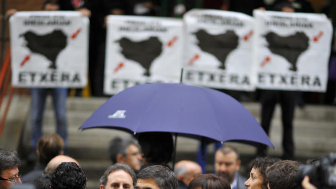 "Basque Regional President or ""Lehendakari"", Patxi Lopez, center, talks to the media after voting, in Bilbao, northern Spain, Sunday Oct. 21, 2012, as pro-independence demonstrators display flags calling to return all prisoners of the Basque armed group ETA to the Basque Country. Almost 4.5 million people will go to the polls Sunday in regional elections in Spain's turbulent Basque region and in northwestern Galicia. (AP Photo/Alvaro Barrientos)"