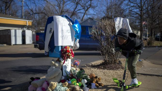 A child rides past a memorial for Antonio Martin, an armed man fatally shot by police late on Tuesday, in Berkeley